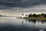 Corran Lighthouse and Lodge under dark clouds in Ardgour on Isle of Mull from the Ferry on Loch Linnhe Scotland UK