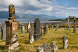 Ancient tombstones at Kilpatrick Cemetery next to Duart Castle on Isle of Mull with sailboats on Sound of Mull at Loch Linnhe Sc