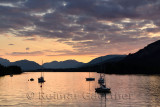 Moored sailboats on Loch Leven with red sky sunset clouds at Glencoe Boat Club and distant Sgurr Dhomhnuill peaks Scottish Highl