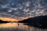 Red Sunset with clouds on Loch Leven with moored sailboats at Glencoe Boat Club and distant mountains of Scottish Highlands Scot
