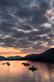 Red Sunset with clouds on Loch Leven with moored sailboats at Glencoe Boat Club Scottish Highlands Scotland UK