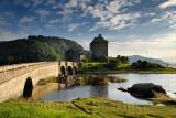Evening sunlight on new stone arch footbridge to restored Eilean Donan Castle on Island at three lochs in Scottish Highlands Sco