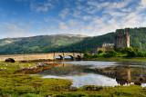 Evening light on restored Eilean Donan Castle with sun on added stone arch footbridge to the Island in Scottish Highlands Scotla