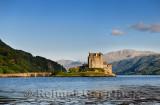 Restored Eilean Donan Castle on Eilean Donan Island with stone arch footbridge at sundown with Glenelg mountains Scottish Highla