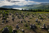 Stone cairns on Highway A87 at Loch Loyne with Spidean Mialach on left and Creag a' Mhaim Highland mountains on right Scotland U