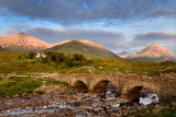 Sligachan Old stone Bridge over River Sligachan with Beinn Dearg Mhor and Marsco peak of Red Cuillin mountains at sunset Isle of