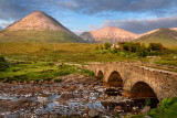 Sligachan Old stone Bridge over River Sligachan with Glamaig and Beinn Dearg Mhor peaks of Red Cuillin mountains at sunset Isle