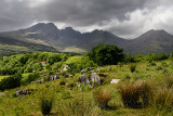 Dappled sun on Blaven mountains of Black Cuillin Hills under dark clouds from Torrin Scottish Highlands Isle of Skye Scotland UK