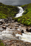 Sun on Blackhill or Eas a' Bhradain waterfall on the Allt Coire nam Bruadaram river with dark clouds Scottish Highlands Isle of