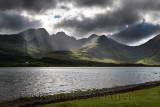 Sun rays on Bla Bheinn mountains outlier of the Black Cuillin with dark clouds and Loch Slapin from Torrin Isle of Skye Scotland