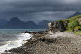 Rocky shore at Port na Cullaidh harbour Elgol with Red Cuillin Mountains under clouds at Loch Scavaig Isle of Skye Scotland UK