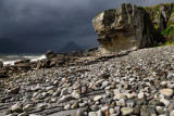 Smooth boulders of Elgol beach at Port na Cullaidh with Red Cuillin Mountains under clouds on Loch Scavaig Isle of Skye Scotland