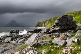 Cliffs and shore north of Elgol Port na Cullaidh with Red Cuillin Mountains under dark clouds on Loch Scavaig Isle of Skye Scotl