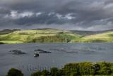 Salmon fish farm net pens on Loch Harport with evening sun on Beinn Dhubh from Portnalong Isle of Skye Scotland UK