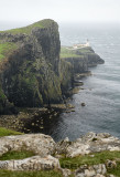 Neist Point Lighthouse in high winds and rain with sheer basalt cliffs to Oisgill Bay Atlantic Ocean Isle of Skye Scotland UK