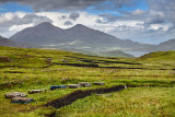 Trenches cut into deep Peat of wetland moors near Drinan on Isle of Skye Scotland with Loch Slap and Beinn Na Caillich mountain