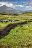 Trench cut into deep Peat of wetland moors near Drinan on Isle of Skye Scotland with Loch Slap and Beinn Na Caillich mountain pe