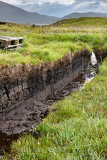 Trench cut into deep Peat of wetland moors near Drinan on Isle of Skye Scotland with Loch Slap to drain water for harvest