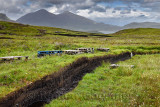 Trenches cut into deep Peat of wetland moors near Drinan on Isle of Skye Scotland with Loch Slap and Beinn Dearg Mhor and Beinn