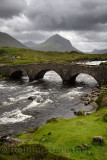 Sligachan Old stone Bridge over River Sligachan with Marsco peak of Red Cuillin mountains after a storm Isle of Skye Scotland UK