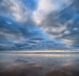 Clouds at sunset reflected in wet sand of wide Inverboyndie Beach with Atlantic Ocean surf at Boyndie Bay Aberdeenshire Scotland