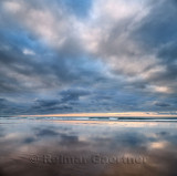 Clouds at sunset reflected in wet sand of wide Inverboyndie Beach with surf at Boyndie Bay Aberdeenshire Scotland UK