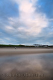 Clouds at sunset reflected in wet sand of Inverboyndie Beach with man running with dog at Boyndie Bay Aberdeenshire Scotland UK