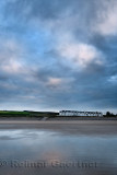 Clouds at sunset reflected in wet sand of wide Inverboyndie Beach with Seabreeze Cottages at Boyndie Bay Aberdeenshire Scotland