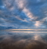 Clouds at sunset and water reflections on wide sandy Inverboyndie Beach at Boyndie Bay Aberdeenshire Scotland UK