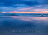 Red sunset and blue sky and surf on wide sandy Inverboyndie Beach at Boyndie Bay Aberdeenshire Scotland UK
