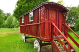 Red painted renovated Gypsy Traveler Caravan parked at the green Cawdor Castle grounds in the rain Nairn Scotland UK