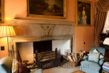 Drawing Room at Cawdor Castle Scotland with plush chairs around fireplace staghead buckle emblem and framed family paintings