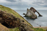 Cave and Bow Fiddle Rock quartzite sea arch with pebble beach at Portknockie on the North Sea Atlantic ocean Scotland UK