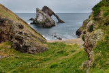 Bow Fiddle Rock quartzite sea arch with pebble beach and cliff with flowers at Portknockie on the North Sea Atlantic ocean Scotl