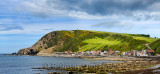 Panorama of single row of houses now holiday lets of Crovie coastal fishing village on Gamrie Bay North Sea Aberdeenshire Scotla