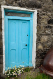 Blue door with daisies of stone house and upside down cauldron in coastal fishing village of Crovie Banff Aberdeenshire Scotland