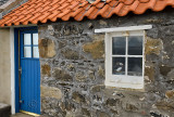 Stone house with blue door and puffin in window in coastal fishing village of Crovie Banff Aberdeenshire Scotland UK