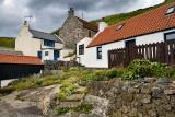 Rock garden and stone houses built into the hillside of coastal fishing village of Crovie Banff Aberdeenshire Scotland UK