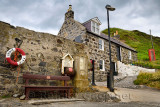Red Telephone booth and Crovie Pier lifebuoy with stone house in Crovie coastal fishing village Banff Aberdeenshire Scotland UK