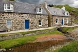 Stream running under a stone house in coastal fishing village of Crovie Banff Aberdeenshire Scotland UK