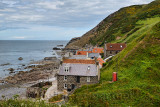 Single row of houses of Crovie coastal fishing village on Gamrie Bay North Sea Aberdeenshire Scotland UK with red telephone box