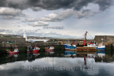 Fishing boats and lighthouse at MacDuff Harbour Shipyards with view of Banff over Banff Bay Aberdeenshire Scotland UK