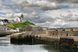 Stone piers at MacDuff Harbour shipyards with Macduff Parish Church on hilltop with clouds Macduff Aberdeenshire Scotland UK