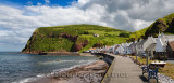 Row of white houses of Pennan coastal fishing village on North Sea in Aberdeenshire Scotland UK with Black Hill sea cliff