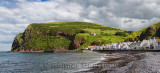 Stone beach and row of white houses of Pennan coastal fishing village on North Sea in Aberdeenshire Scotland UK with Black Hill