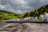 Stone beach and row of white houses of Pennan coastal fishing village on North Sea in Aberdeenshire Scotland UK with green sea c