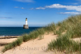 Rattray Head Lighthouse in the North Sea at Buchan Aberdeenshire Scotland with sea grass on sand dunes and sandy beach
