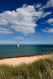 Rattray Head Lighthouse in the North Sea at Buchan Aberdeenshire Scotland with blue sky and white cloud from sea grass sand dune