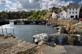 Stone pier walls at Crail Harbour with fishing boats and lobster traps and cliff with beach at Crail Fife Scotland UK