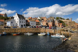 Stone ramp and pier walls at Crail Harbour with fishing boats and lobster traps in Crail Fife Scotland UK